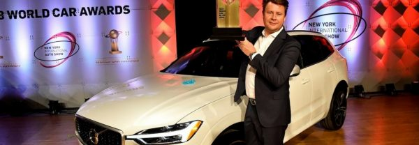 A man in front of a Volvo car at the New York International Auto Show