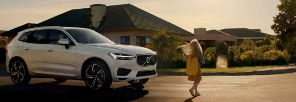 White Volvo XC60 parked in front of a house at sunset with girl walking in front of it