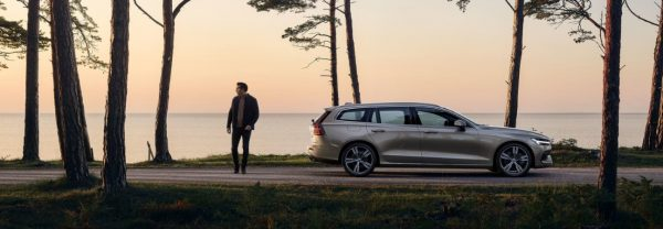 Silver 2019 Volvo V60 parked in a wooded area next to a lake.