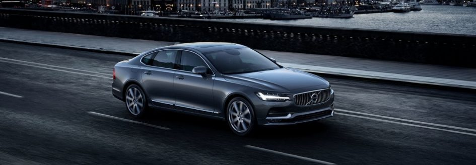 2019 Volvo S90 in gunmetal gray driving across a bridge in a city.
